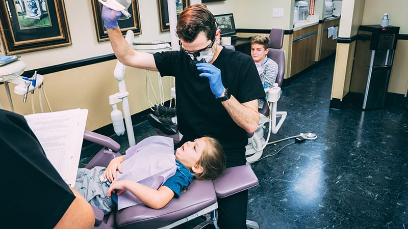 Dr. Bobby Stanislawski a Pediatric Dentist checing on a child's tooth